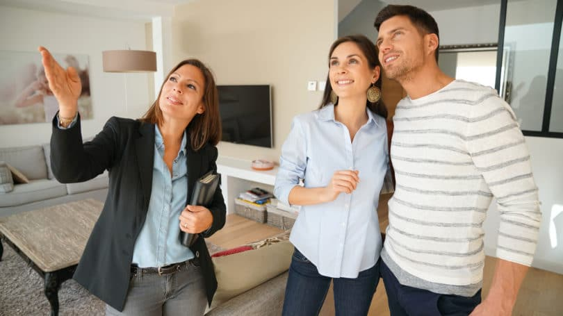 Real Estate Agent Showing House To Happy Couple